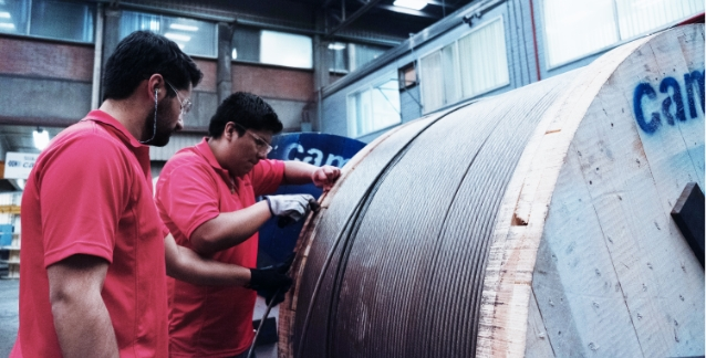 two men in red shirts inspecting a spool of cable